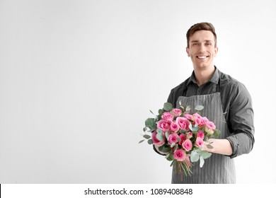 Male florist holding bouquet of beautiful flowers on light background