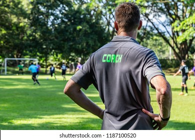 Male football or soccer coach watching his team play at a beautiful soccer field with larger background trees