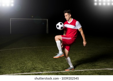 Male footballer playing football, kicking a ball with his knee on soccer field.