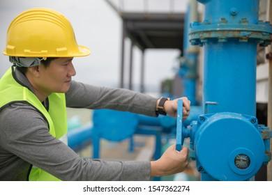 Male foreman wearing yellow safety helmet turning big valve