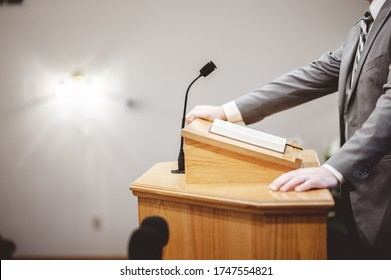 A male in a formal outfit preaching the Holy Bible from the tribune at the altar of the church