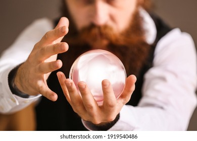 Male fortune teller with crystal ball reading future, closeup