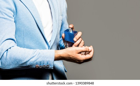 Male fragrance and perfumery, cosmetics. Man perfume, fragrance. Man in a suit. Perfume or cologne bottle. Masculine perfume. Man holding up bottle of perfume. Fashion cologne bottle. Copy space.