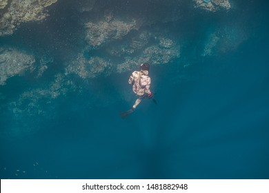 Male free diver wearing a camouflage wetsuit ascends to the surface after a deep underwater cliff dive in Pescador Island, Moalboal.