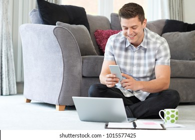 Male Freelance Worker Using Mobile Phone At Home