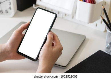 Male freelancer or business man hands using mobile phone with blank white screen for mock up at home office table. Work at home concept.