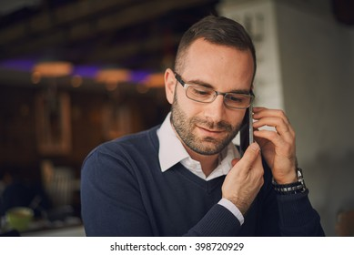 Male freelancer connecting to wireless via laptop computer/smart phone, thoughtful businessman work on notebook while sitting at wooden table in modern coffee shop interior