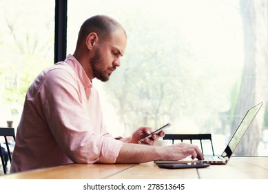 Male freelancer use notebook sitting in modern loft interior with big windows, confident business man busy using laptop at office desk, young student typing on computer while sitting at wooden table
