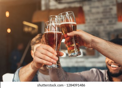 Male friends clinking beer glasses, sitting in bar, closeup