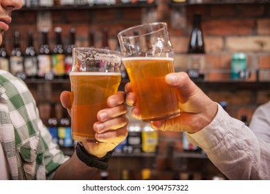 Male friends clinking beer glasses at the pub