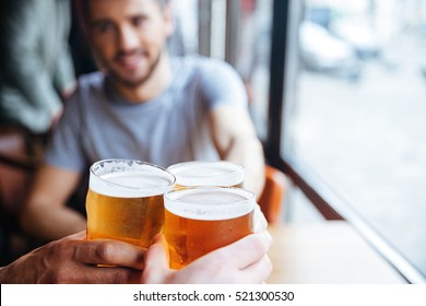 Male friends clinking with beer mugs in pub