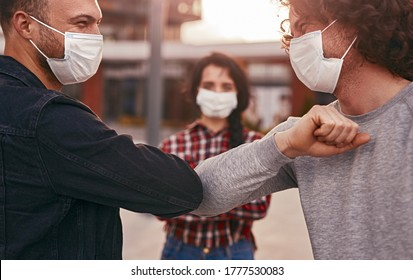 Male friends in masks doing elbow bump while greeting each other during coronavirus pandemic