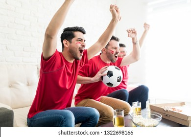 Male friends showing support towards their loved soccer team while watching TV
