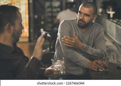 Male friends sitting at bar counter and communicating. Men talking, spending time together and enjoying elite alcohol. Male clients of bar holding glasses of whisky or scotch.