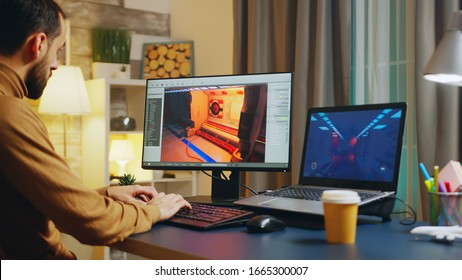 Male game developer typing on keyboard while developing a new level of the game.