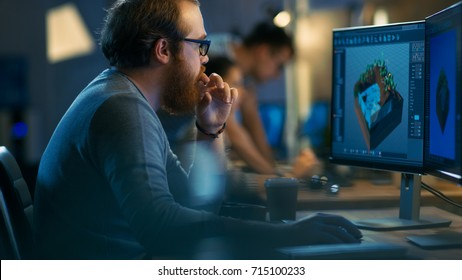 Male Game Developer works on a Level Design on His Personal Computer with Two Displays. He Works for in a Creative Office Environment with Very Talented Colleagues.