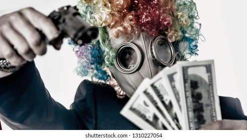 Male gangster in the mask clown with gun takes the money. Criminal concept.
