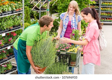 Male garden centre worker selling potted plant to female customers