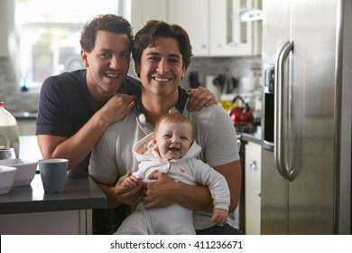 Smiling gay couple with daughter sitting outdoors Gay Couple