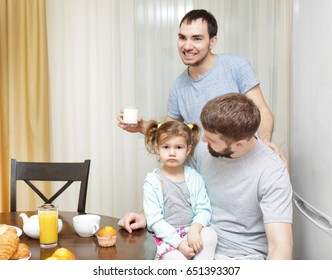 Male gay couple with daughter having breakfast in kitchen