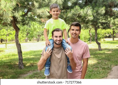 Male gay couple with foster son having fun in park. Adoption concept