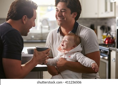 Male gay couple holding baby girl in their kitchen