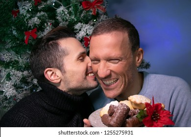 Male gay couple kissing, smiling, laughing in front of christmas tree with plate of cakes