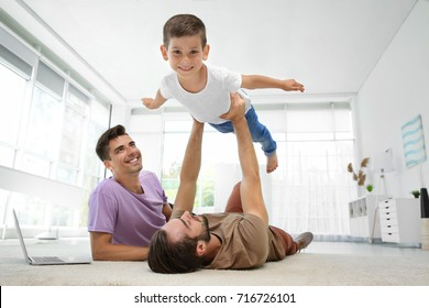 Male gay couple playing with foster son. Adoption concept