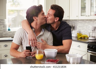 Male gay couple in their 20s kissing in their kitchen