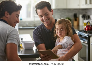 Male gay dads use tablet with daughter in kitchen, close up