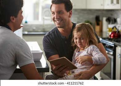 Male gay dads using tablet with daughter look at each other