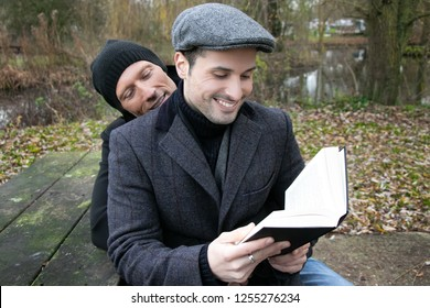 Male gay husbands sit on park bench to read to each other from book