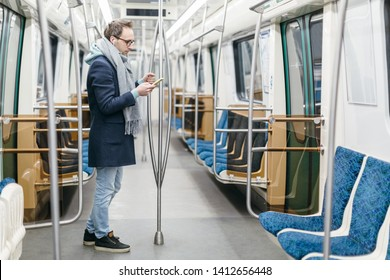 Male with glasses and wireless headphones rides in the subway train. He is wearing a blue coat and a gray scarf, holding handrail and using smartphone. Digital dependence, social networks addiction.