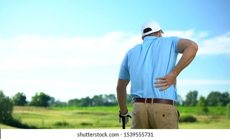 Male golf player feeling strong lower back pain after ball hitting, trauma