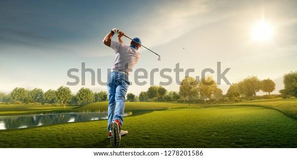 Männlicher Golfspieler auf professionellem Golfplatz. Golfer mit Golfklub auf Schuss
