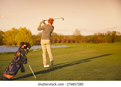 Male golf player shooting ball on fairway at sunset.