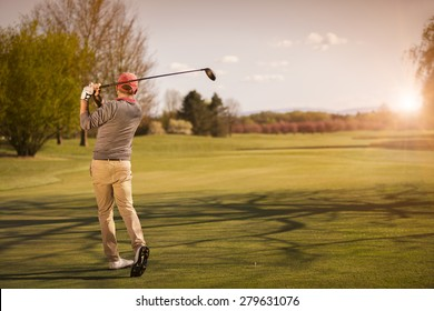 Male golf player swinging golf club for tee shot at beautiful sunset.