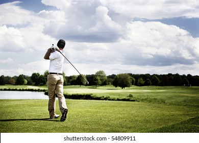 Male golf player teeing off golf ball from tee box, wonderful cloud formation in background.
