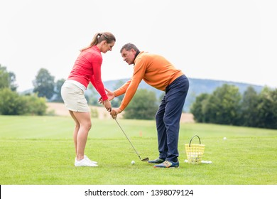 Male golfer giving training to woman for taking a shot on golf course