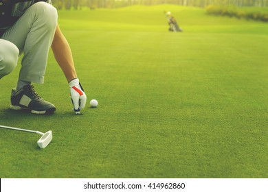 Male golfer marking ball position on the green. Focus on  pitchmark