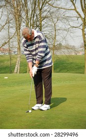 male golfer putting on the green