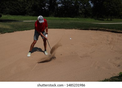 Male golfer in a sand bunker, playing the golf ball. Swinging the golf club, sand fountain in the air. Flying golf ball. Motion blur of the sand and ball. No other persons. Sunny day. Space for text.