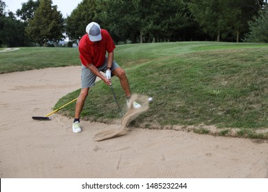 Male golfer in a sand bunker, playing the golf ball. Swinging the golf club, sand fountain in the air. Flying golf ball. Motion blur of the sand and ball. No other persons. Summer day. Space for text.