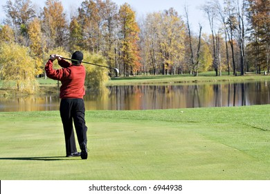 A male golfer smartly dressed in a red sweater is enjoying  a round of November  golf.