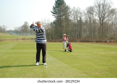 male golfer teeing off while female golfer is watching in background