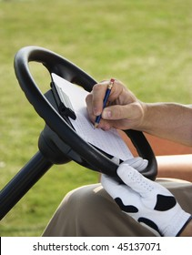 Male golfer writing his golf score while sitting in a golf cart. Vertical shot.