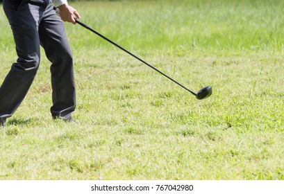 Male golfers are showing their beautiful golf swing on green grass in the park. With nature background