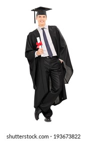 Male graduate holding a diploma and leaning against a wall isolated on white background