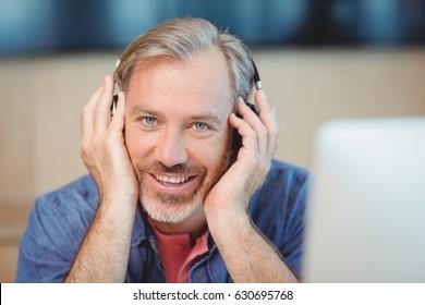 Male graphic designer listening music on headphones in office