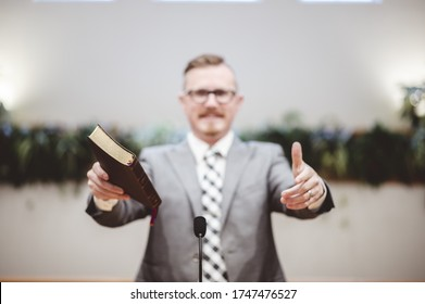 A male in a grey suit preaching words of the Holy Bible at the altar of a church